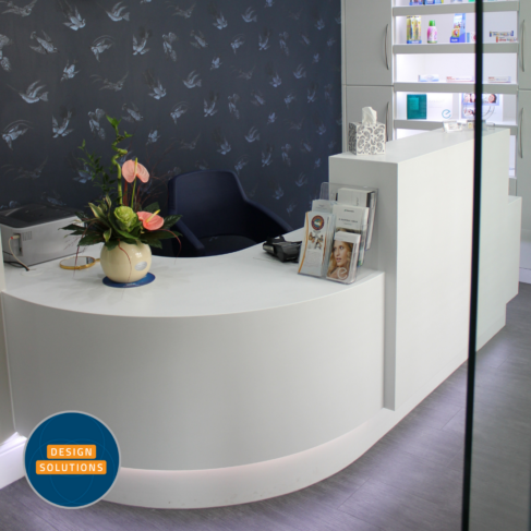 Bespoke Dental Reception Desk with white Corian with high area for screen to be hidden