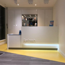 Bespoke Dental Reception Desk in white and grey corian with logo and lighting